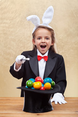 Happy magician girl conjuring colorful easter eggs