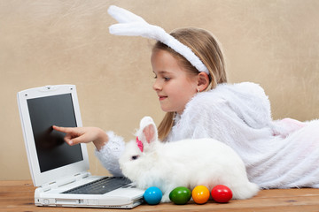 Little girl with her bunny using computer together