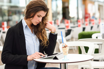 Woman looking at her tablet computer siting in a bar