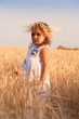 Girl in a white dress to stand in the field of ripe wheat