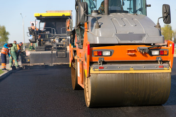 Road construction works with roller compactor machine