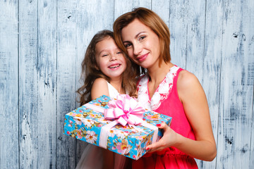 little girl giving her mom a present , the day of mothers