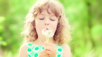 Happy child blowing dandelion in spring outdoors. Slow motion