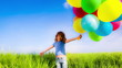 Happy child playing with multicolor balloons in spring field. Sl
