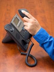 close up shot of human hand holding landline phone receiver