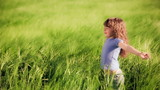 Happy child enjoying in spring field. Slow motion