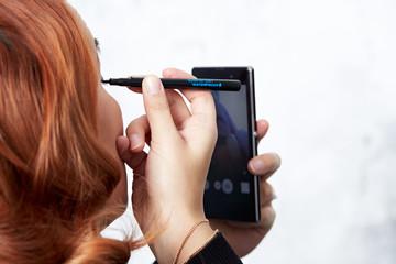 junge frau schminkt sich am smartphone