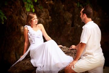 groom looks at bride sitting on rock at sand beach