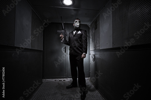 Male with the rifle and gas mask in an old elevator - 77802606