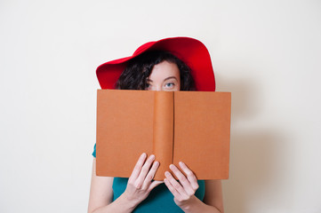 Young woman with red hat reading book face partially covered