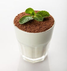 tiramisu in a glass with chocolate with spoon and green leaf