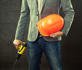 Portrait of construction master holding yellow helmet