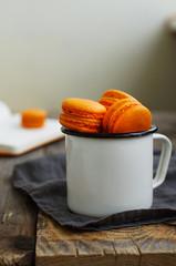 White metal cup full of orange colored mango macaroon