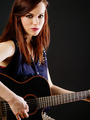 Young beautiful woman playing acoustic guitar