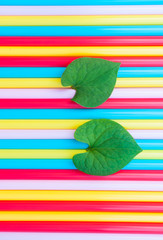 Heart-shaped leaves on Background of colorful straws
