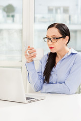 Caucasian businesswoman is working with notebook while drinking