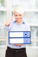 Businesswoman making positive thumb gesture while holding pile o