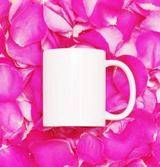 White mug on petals of pink roses background