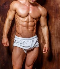 Bodybuilder psoing in the studio.