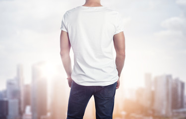 Man in white t-shirt on blurred city background