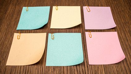 Six colorful post-it notes on wooden background.