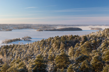 View over snowy trees, frozen lake & islands in in Tampere