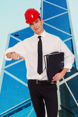Young nice guy in hardhat with a folders