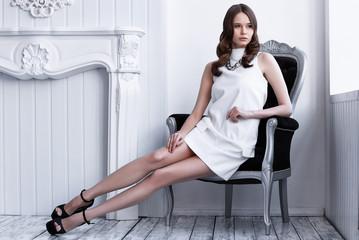 High fashion shot of young beautiful woman in white short dress