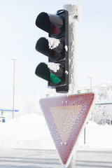 Frozen traffic light at winter showing red light
