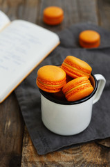White metal cup full of orange macaroon cookies