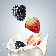 Blackberry and strawberry fall into milk splash