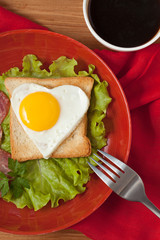 Fried heart shaped egg on toast with salad and coffee for Valent