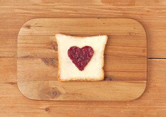 Slice of wholewheat toast with berry jam in the shape of heart o