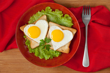Two fried heart shaped eggs on toast with salad and coffee for V