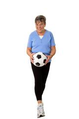 Seniorin  läuft mit Fußball