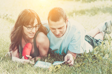 Young boy and girl reading a book on the grass in the park