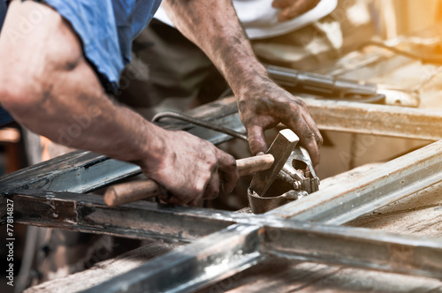 Dirty worker hands doing hammer work on construction site - 77814827
