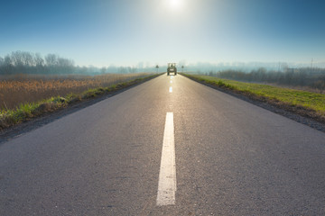 Asphalt road towards sun and upcoming tractor