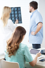 Doctors reading MRI and electrocardiogram