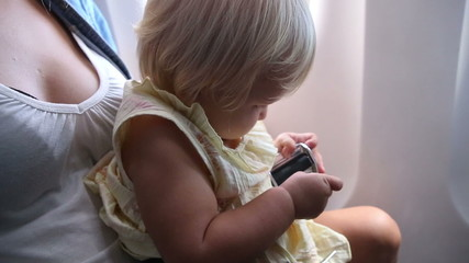 little child play with safety belt buckle in airplane