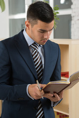 Young asian caucasian business man holding a book