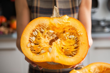 Closeup on young housewife in kitchen showing half of pumpkin