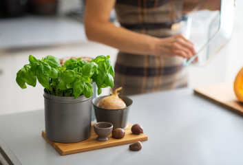 Closeup on fresh basil on table and housewife in background