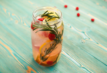 Detox water with citrus, raspberry and rosemary in jar