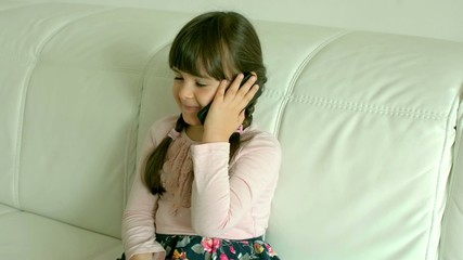 little girl sitting on sofa and talking on the phone