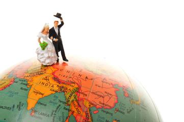 地球儀の上に立っている結婚した二人のカップル