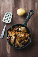 Frying pan with roasted unpeeled potato and champignons