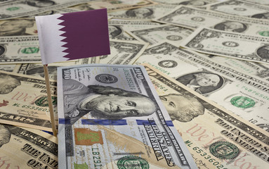 Flag of Qatar sticking in various american banknotes.(series)
