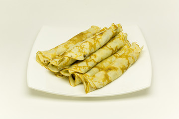 The Russian pancakes on a plate are isolated on a white