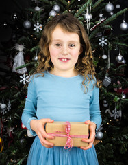 small girl holding present with christmas tree behind